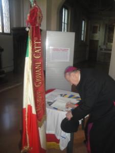 E. Mons. G. Merisi firma il registro delle dediche.